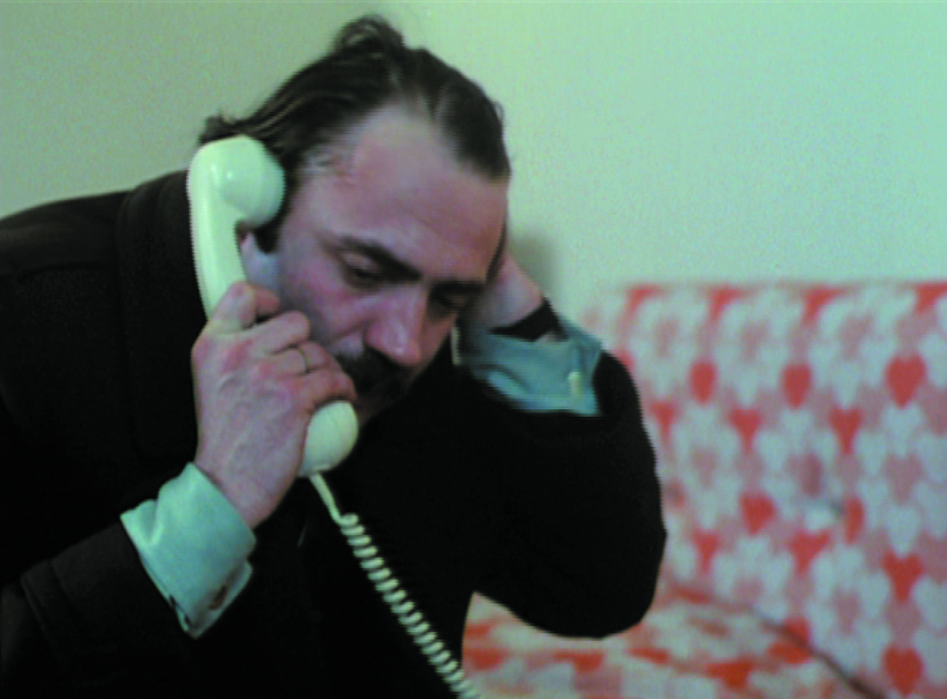 In this video still, a man makes a phone call with a white cord phone while he nervously runs his other hand through his already somewhat light dark hair. Behind it there is a sofa with a white-red flower pattern.