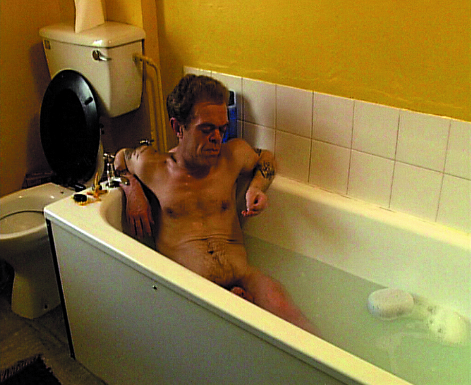 This still shows a runtish man naked in a filled bathtub. He looks lost in thought at his right hand.