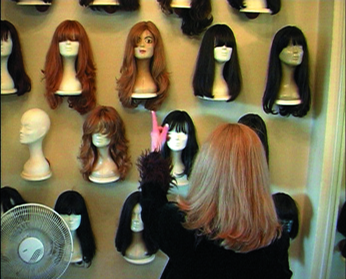 This video still shows the rear view of a woman with long light brown hair standing in front of a shelf and pointing with her left index finger at one of the various wigs on mannequins displayed there.