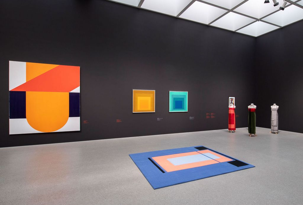 Exhibition space of the Pinakothek der Moderne with geometric-abstract paintings by Takesada Matsutani and Josef Albers, as well as textile works (carpet, clothes) by Andrea Zittel, Sammlung Goetz, Munich