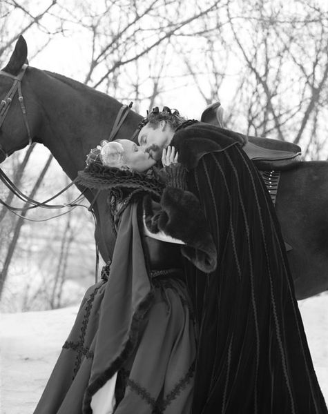 This black and white photograph shows a woman and a man in wintery renaissance clothing, standing in front of a horse and kissing passionately.