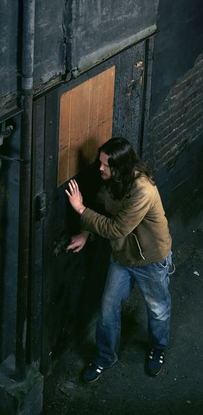 The photograph by artist Jeff Wall shows a long-haired and bearded man who is about to open a door in a dark alley. He seems to be listening and above all cautious. The photograph seems to have been taken from the perspective of an upper apartment on the opposite side.