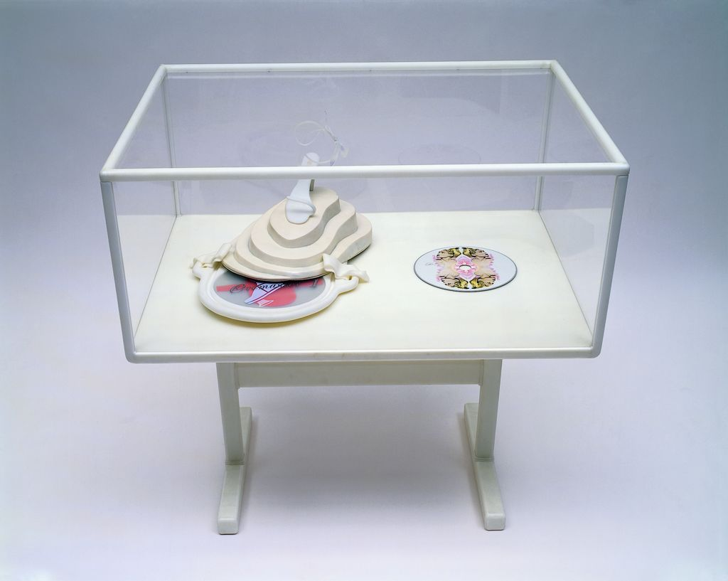 This photograph shows a display case with white edges and a frame in which a white object is placed, on which a white and open high heel is standing. On the right side there is a CREMASTER 1 DVD with the artwork of a person from the film on it.