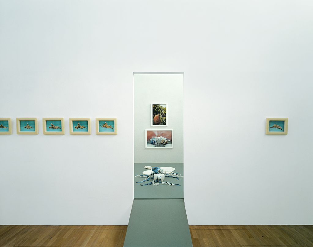 This installation view shows works related to Cremaster 4 and Drawing Restraint. On the left are photographs of mythical creatures against a light blue background. In the middle, an object from Cremaster 4 is laid out on a grey surface on the wooden floor. Above it photographs of the same work are hanging. To the right is a single photograph from Drawing Restraint.