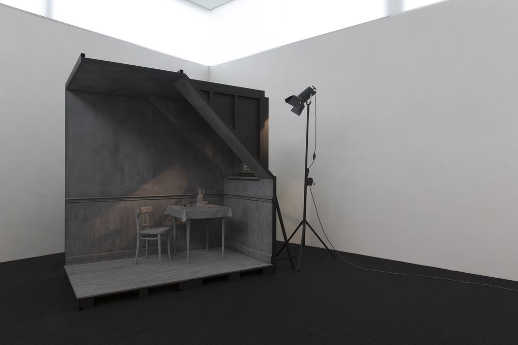 The installation view shows a grey, true-to-scale model of a room corner with a chair, a laid table and a window through which artificial light falls from an outside lamp.