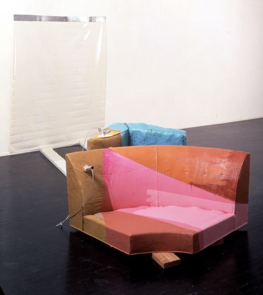 This installation consists of the corner part of a couch, further couch cushions, iron parts, wooden planks and a two-dimensional object on the wall, which was fixed with adhesive tape.