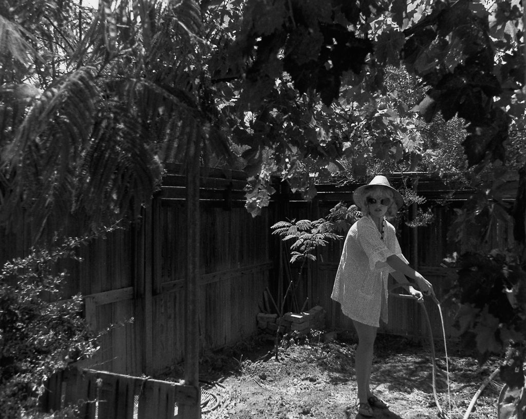 Black and white photograph, woman looks up torwards the viewer while watering her garden