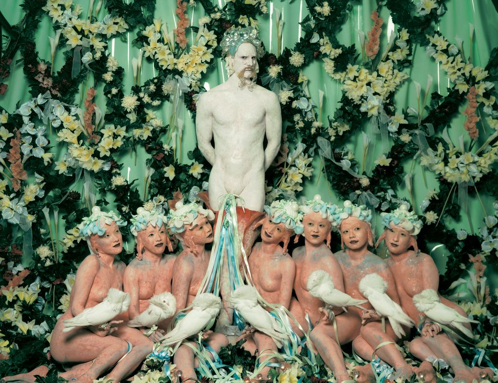 Here you can see a production still from the Cremaster series of the artist Matthew Barney. In front of a flower wall stands a man, painted white and looking like a faun. In front of him sit seven undressed women with strange looking ears and headdresses. They each hold a rare white pigeon on their hand.