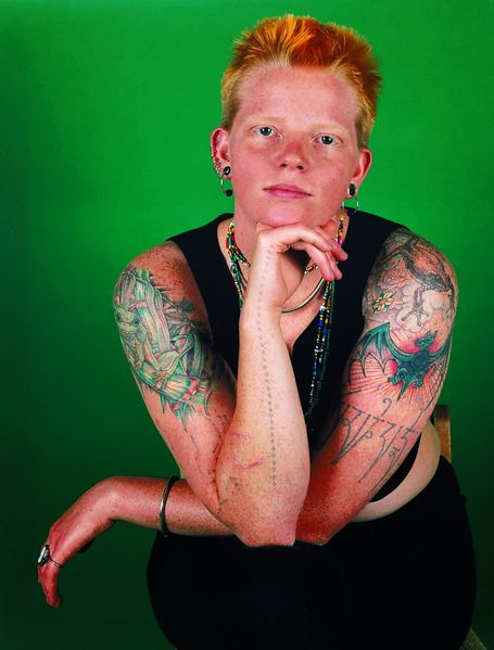 Here is a portrait photograph of a red-haired woman with short haircut and tattooed upper arms in front of a green background. She is sitting on a chair, her legs crossed, her elbows leaning on her knees, one hand on her chin and looking directly into the camera.