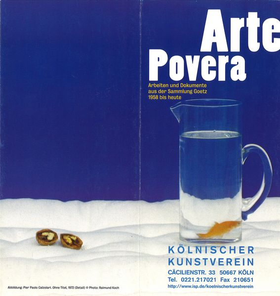 This invitation card shows a section of a work by Pier Paolo Calzolari. In the background is blue canvas and in the foreground parts of the snow-white mattress, two halves of a walnut and a carafe of water with a goldfish in it.