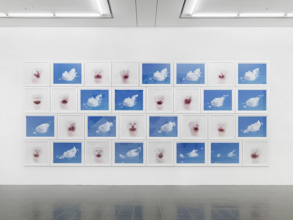 This installation photo shows an arrangement of photographs, alternating between clouds in a rich, blue sky and blurred clown faces.