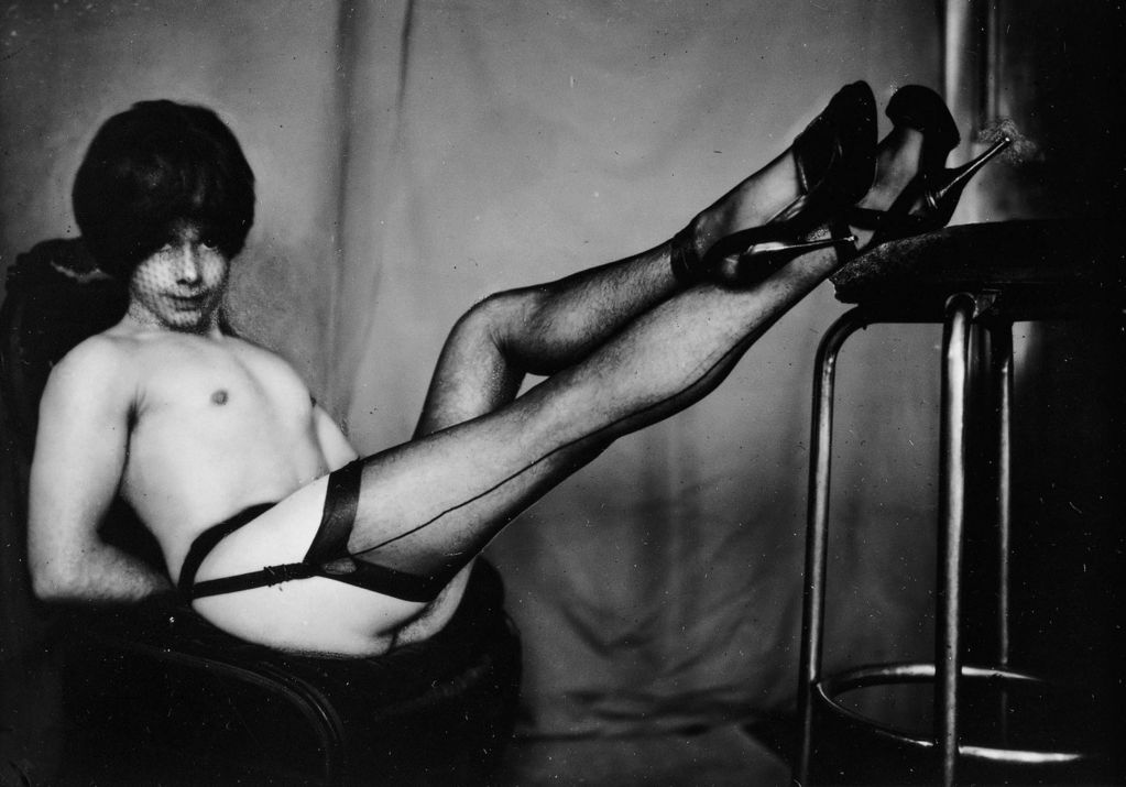 This black and white photography includes a complete shot of a man with face net and wig, garter belt and stockings as well as high heels, who looks lasciviously into the camera. He sits with his arms behind his back on a cantilever chair and has put his feet on a bar stool.