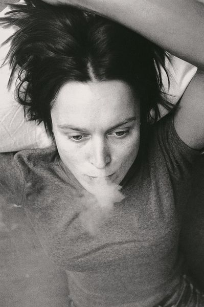 This black and white photograph is a self-portrait of the artist Sarah Lucas seen from above. She is lying in bed smoking a cigarette with one arm above her head.