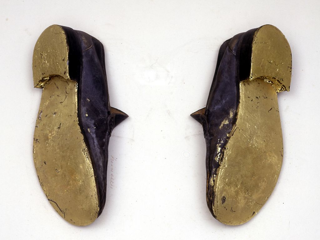 A pair of black leather slippers with gold leaf covered soles that seem to be hung on the wall.