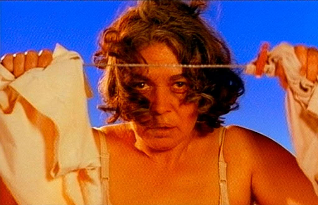 In this video still, a middle-aged brunette woman looks between two pieces of clothing hanging on a clothesline. The coloration appears unnaturally saturated.