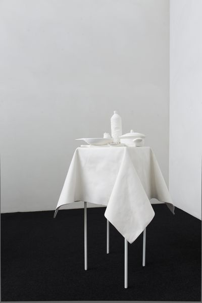 A white plaster table with long, thin table legs stands on a black ground in the lower right center of the image. The table itself is covered with a tablecloth that casts even wrinkles over the edges of the table, on top of which are a bottle, a small plate, a pot with a lid and a large plate. The complete model is made of white plaster, the background is painted white.